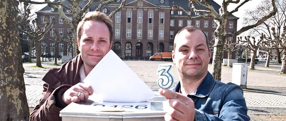 Zwei Mitarbeiter aus dem städtischen Wahlteam weisen auf die drei Wahlen am Sonntag, 25. Mai, hin. © Michael Paternoga