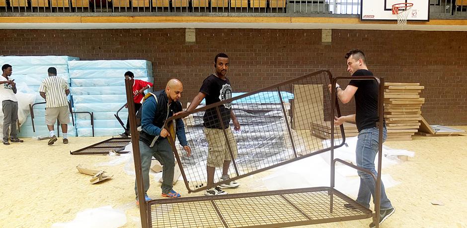 Mitarbeiter von European Homecare beim Aufstellen der Betten in der Sporthalle. © Stadt Herne, Horst Martens