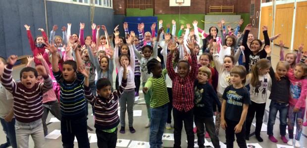 Kinder der Schule an der Schulstraße singen und tanzen auf der Bühne.