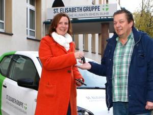 Dr. Sabine Edlinger, Mitglied der Geschäftsleitung der St. Elisabeth Gruppe – Katholische Kliniken Rhein-Ruhr, überreichte Rüdiger Hoh, Stadt Herne, den Schlüssel für den VW Up. Dieser kann von Mitarbeitern der Stadt für ein Jahr kostenlos für Fahrten rund um die Betreuung der Flüchtlinge eingesetzt werden.