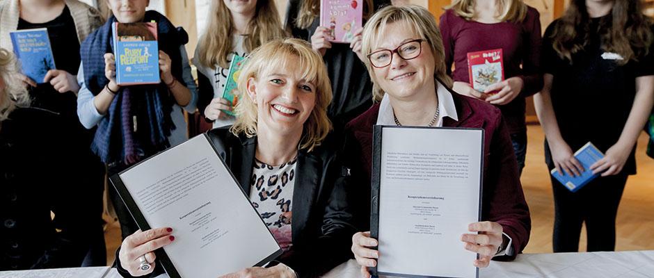 Schulleiterin Nicole Nowak und Karin Anlauf, Leiterin der Stadtbibliothek, besiegeln die Zusammenarbeit. © Frank Dieper, Stadt Herne.