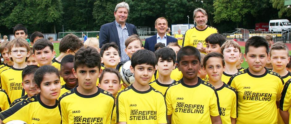 """Bildzeile: """"Reifen Stiebling""""-Geschäftsführer Christian Stiebling mit Schirmherr Olaf Thon und Fußball-Camp-Trainer Lothar Woelk (hintere Reihe von links)."""