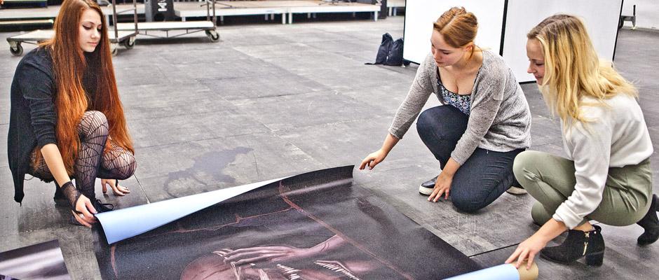 Die HERBERT-Mitarbeiterinnen Judith Mehlich (r.) und Anna-Lotta Iserloh (M.) schauen sich interessiert das Bild an, das die Künstlerin Johanna Falchi in der Ausstellungshalle ausrollt. © Horst Martens, Stadt Herne