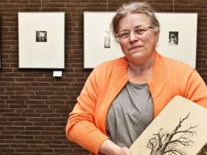 Petra K. Engel mit einer Lithografie vor der Ausstellungswand. ©Stadt Herne, Horst Martens.