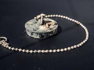 Im Jahr 4022 entdeckt: Der formschöne Anhänger wurde aus gummi geschnitzt und ist über einen silbernen Ring mit einer wunderschön gearbeiteten silbernen Kette verbunden. Das Amulett wurde am Boden eines weiß poliertenn Sarkophags gefunden. ©Thomas Schmidt, Stadt Herne