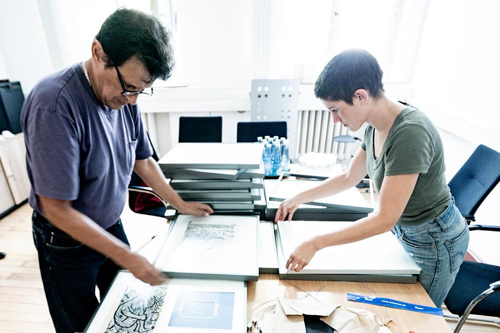 Der Künstler Daniel Pulido und Sabrina Locuratolo rahmen Bilder für die Ausstellung ein. ©Frank Dieper, Stadt Herne.