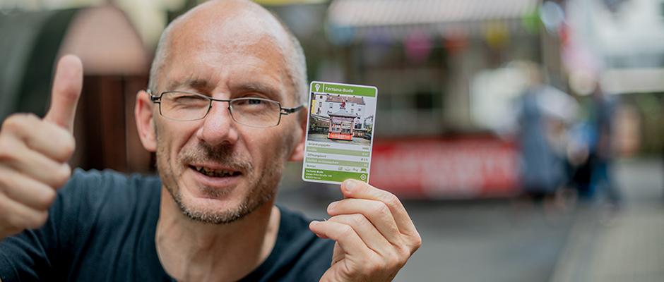 Museumsleiter Ralf Piorr spielt mit offenen Karten. Hier geht es um ein Exemplar aus dem Trinkhallenquartett. ©Frank Dieper, Stadt Herne.
