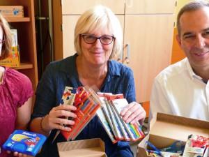 Ansgar Montag von der Caritas übergibt Material an Claudia Huhmann-Rohkämper (stellvertretende Leiterin) und an Monika Müller (Leiterin) von der Grundschule Kunterbunt.