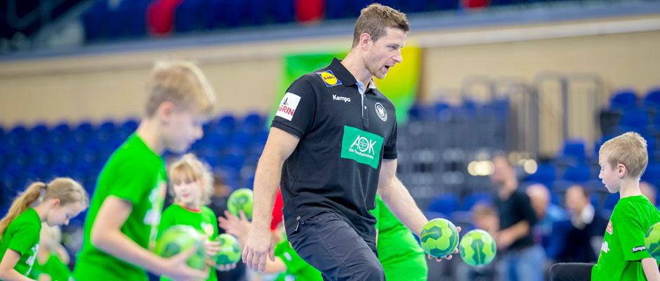 Beim AOK Star-Training zeigt Handball-Star Martin Strobel den Schülerinnen und Schülern verschiedene Dribbel- und Schritt-Techniken. Foto: Sascha Klahn/ DHB